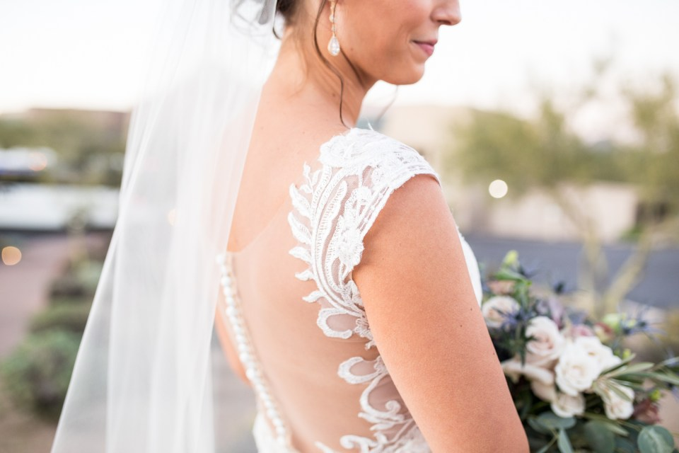 desert wedding bride with large succulent bouquet and lace illusion back wedding dress by eddy k