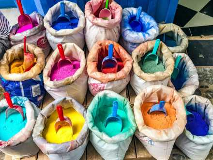 Colourful bags of dye line the marketplace