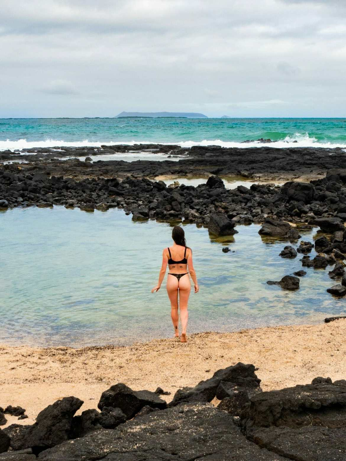 Girl in bikini walking on beach with black volcanic rocks Galápagos