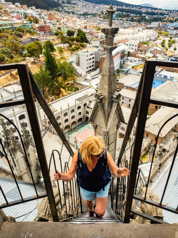 Woman climbing up ladder to Basilica del Voto Nacional church in Quito