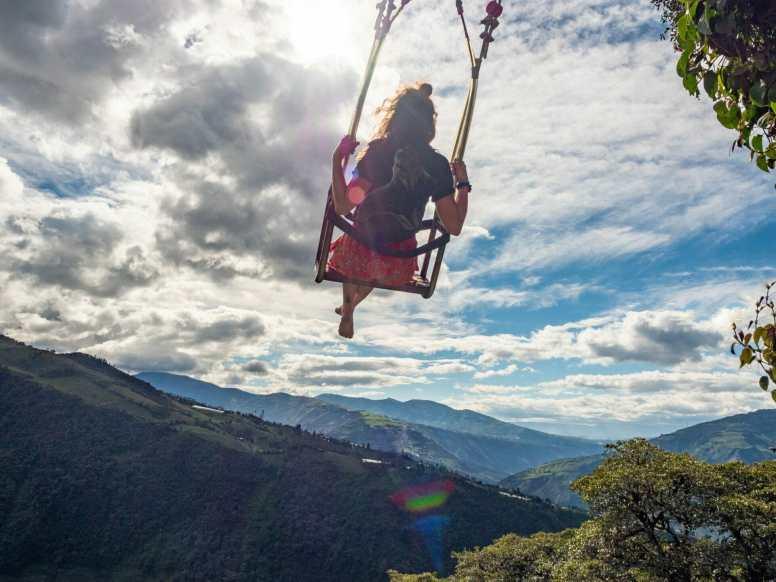 Girl swinging over mountains in Baños Ecuador