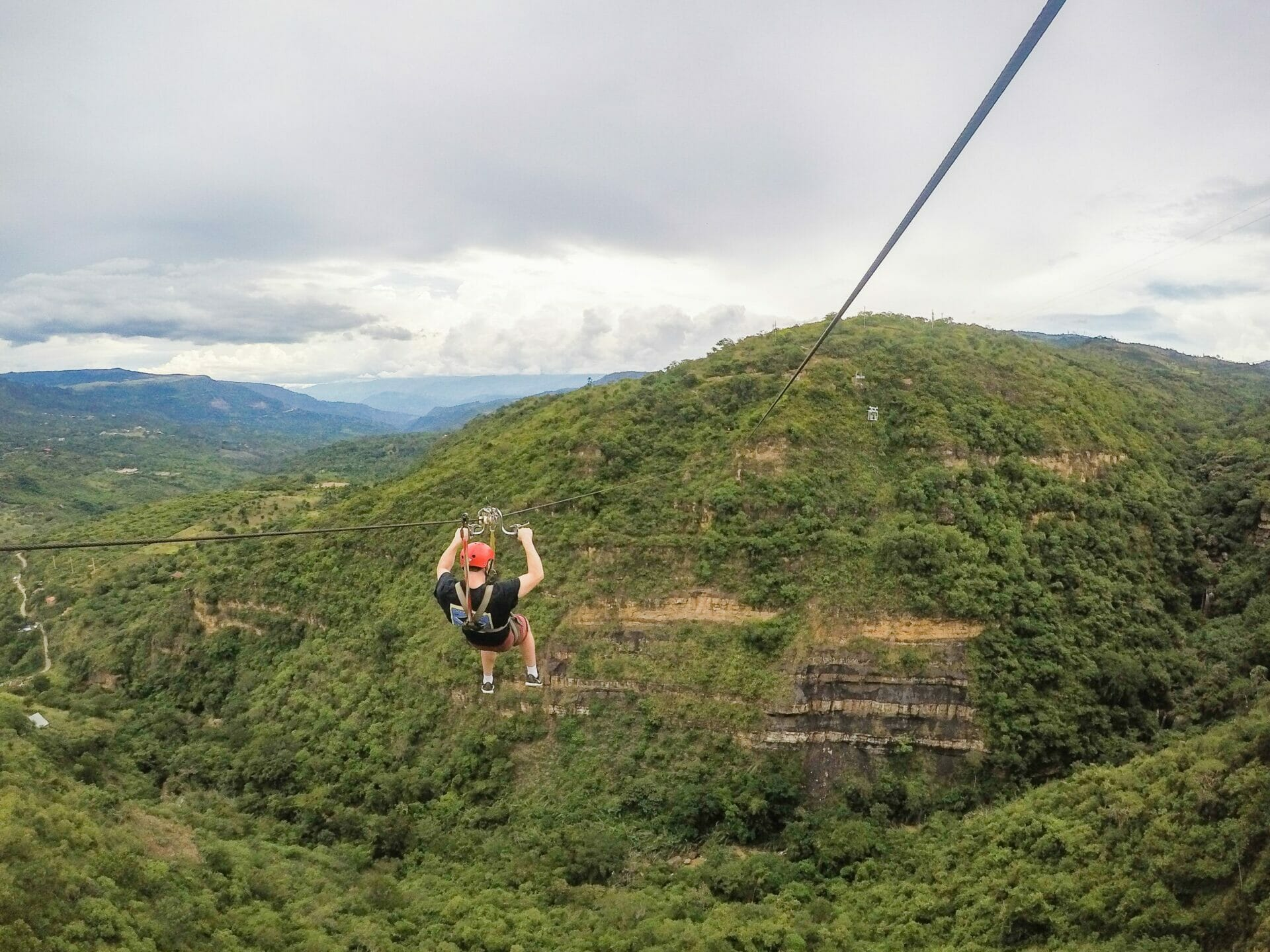 Man ziplining over green canyon San Gil Colombia