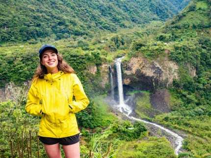 Girl smiling at Cascada Manto de la Novia waterfall Baños Ecuador