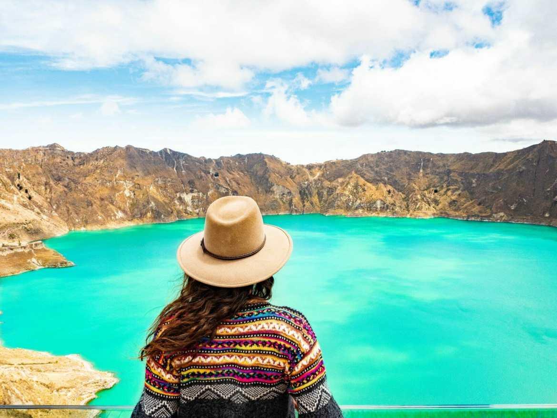 Girl looking at Laguna Quilotoa turquoise lake Ecuador