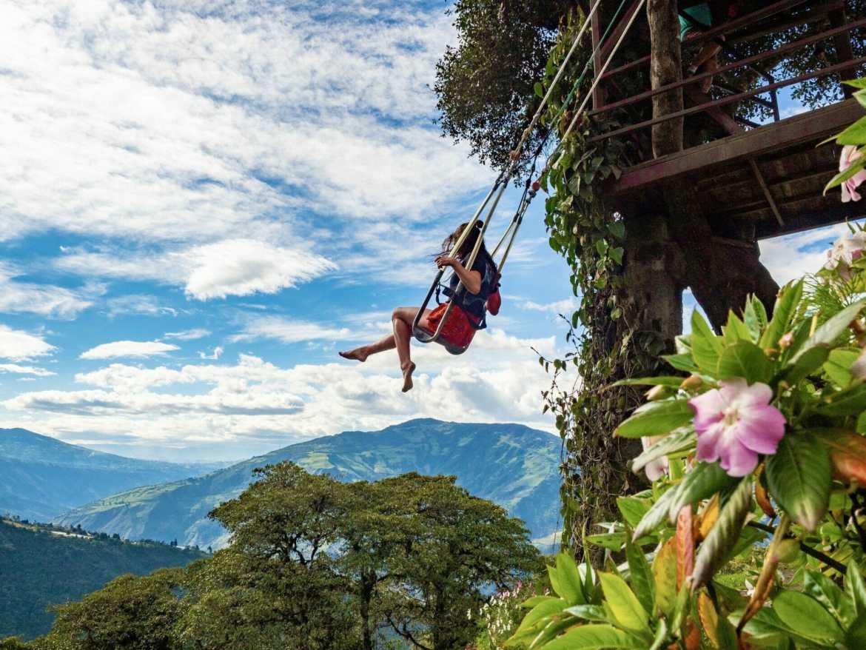 Girl swinging over mountains Casa del Arbol Baños