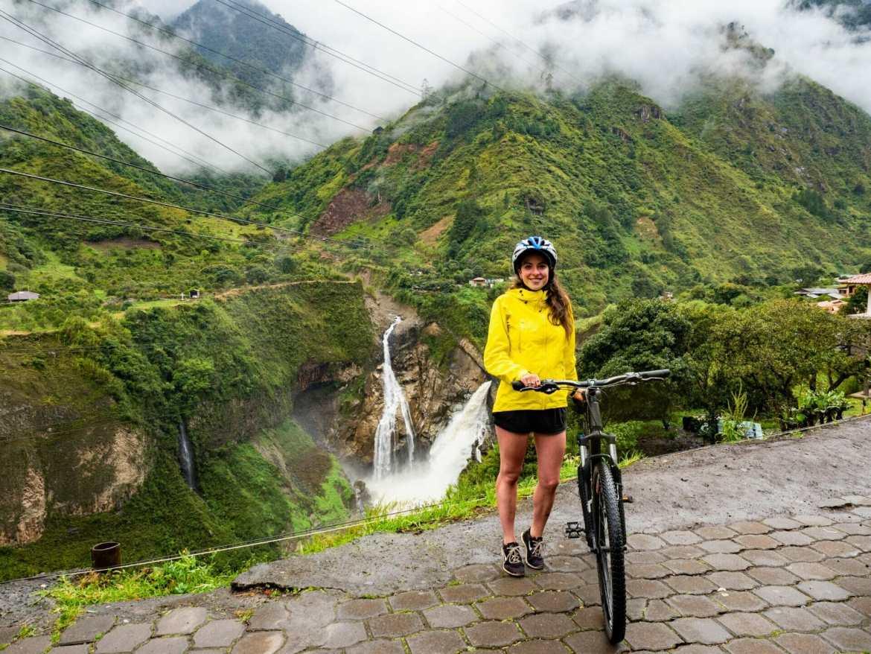Girl with bike in front of waterfall Baños Ecuador