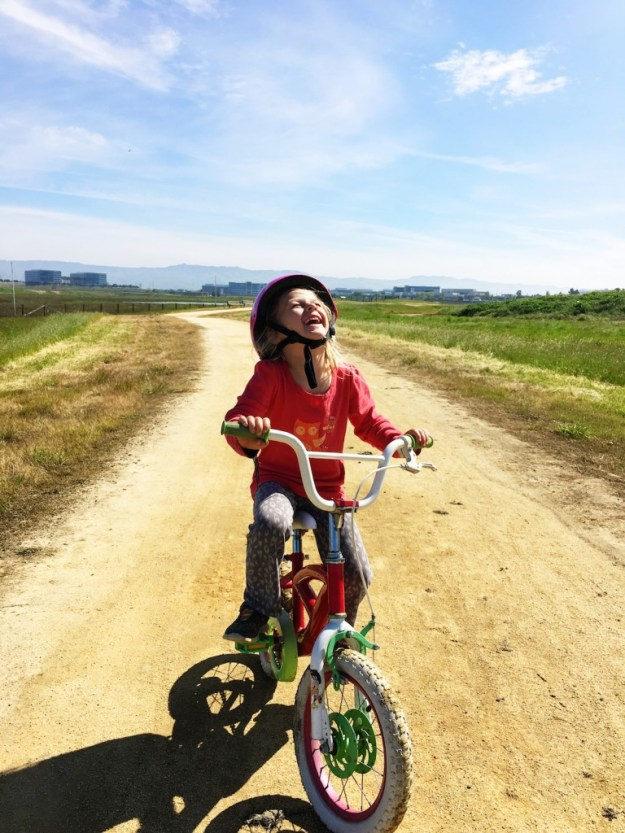 Lillian smiling while riding a bike