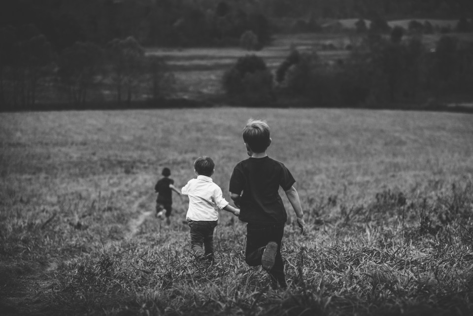 boys running in a field, b/w