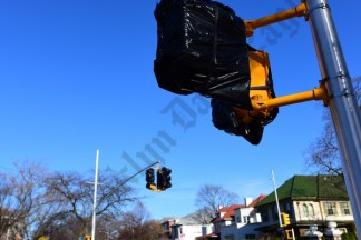 Covered signal lights awaiting unveiling at the intersection of Avenue J & Ocean Parkway, which residents & officials claim will make navigating the area extremely difficult. - Brooklyn Archive