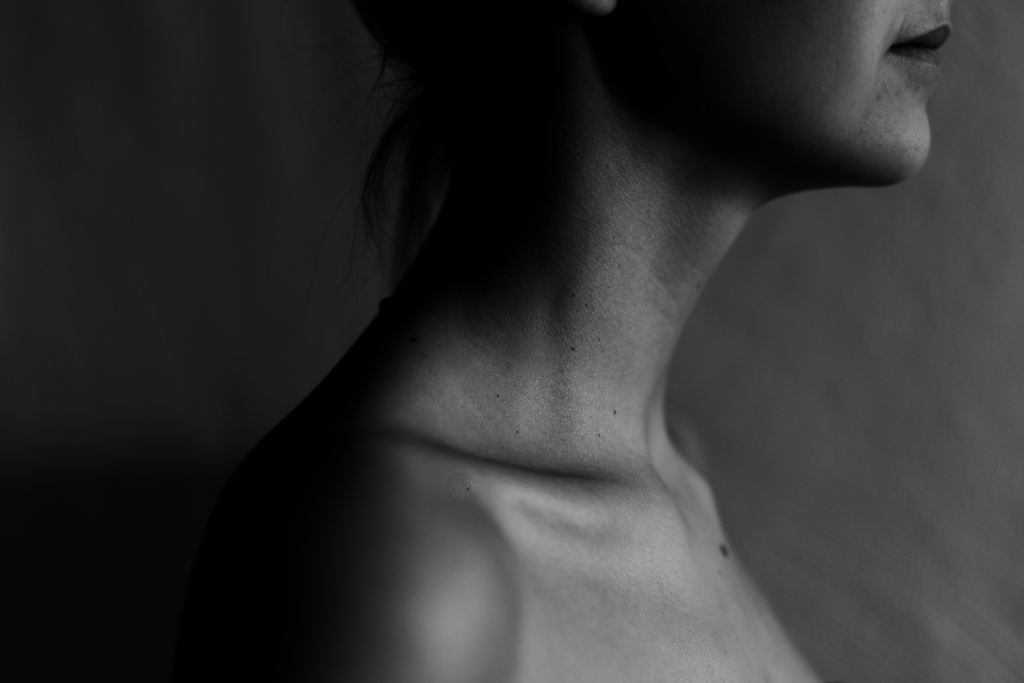 A black and white photo of the profile of a woman's bare shoulder, neck and chin