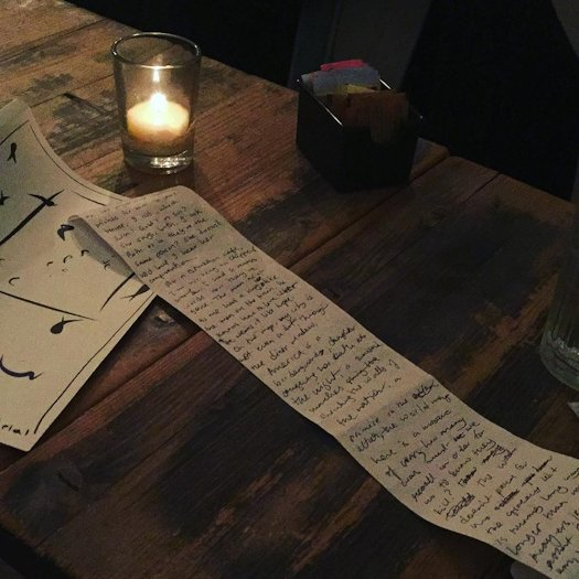 Candle-lit tabletop with a poem draft written by hand on the back of a long, narrow receipt sheet.