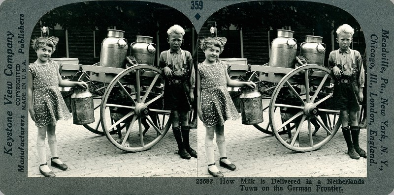 Two children stand next to a dog-drawn cart containing huge containers of milk.