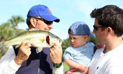 """Larry Winston, """"assisted by"""" his great grandson in landing another Brooks big bass"""