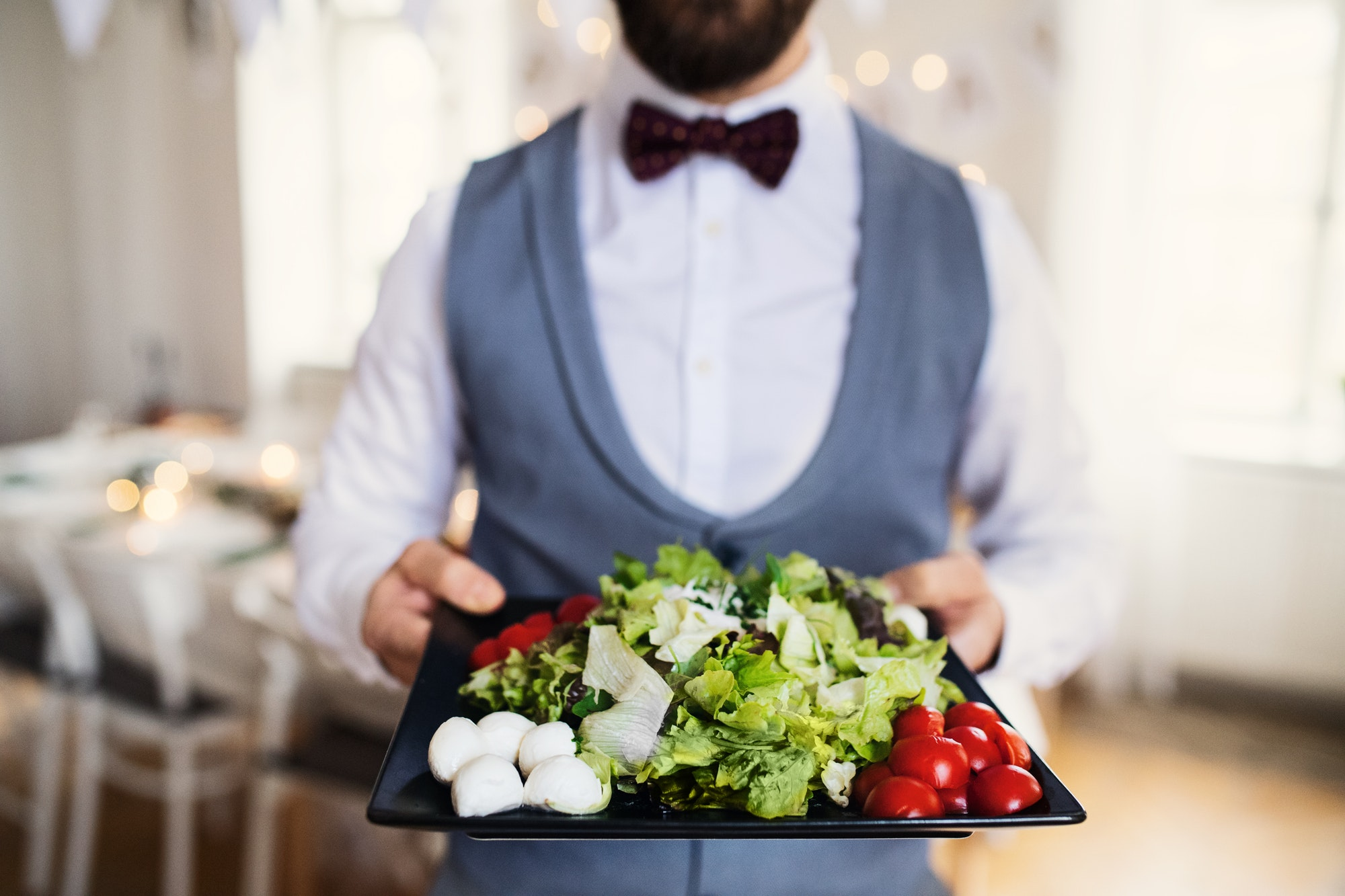 Midsection of man standing indoors in a room set for a party, holding a tray with vegetables.