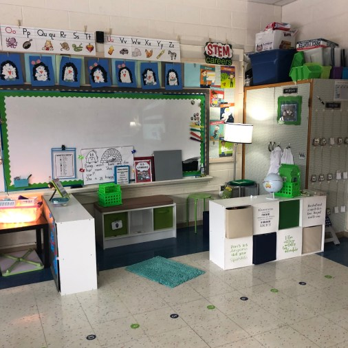 A classroom corner set up with white stoage bins. A whiteboard with magnets. A sensory table with rice in the corner under a lamp. STEM Careers displayed on the wall.
