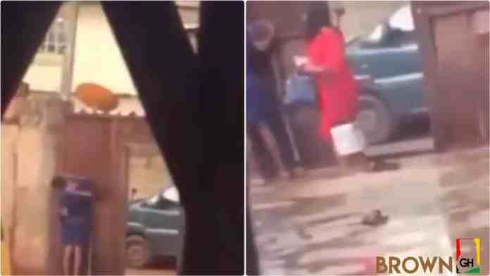 Mother catches daughter 'chopping' love with a man in their compound and slaps her(Video)
