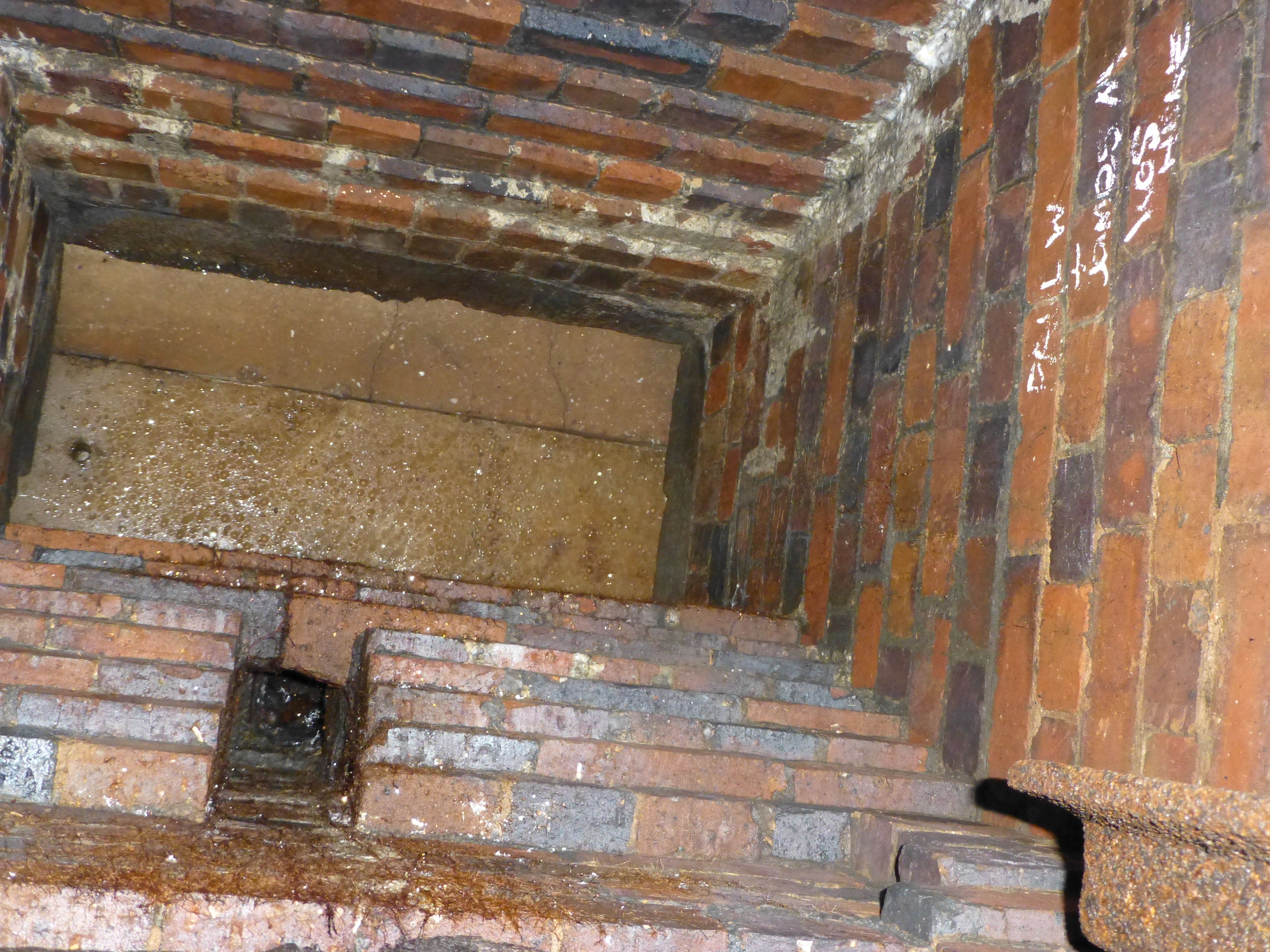 Looking upwards to ground level above the chamber. The top is blocked with planks or slabs, and there are guide rails and a control channel for the gate mechanism.