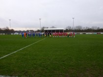 Molly and the home team, in red strip, welcome the visitors and match officials