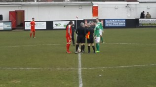 Captains shake hands and the three men in black complete the scene.