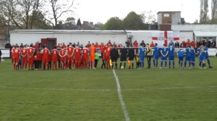 The visitors, Paget Rangers,played in blue strip, on a beautiful green grass pitch, surrounded by lines of supporters in red.