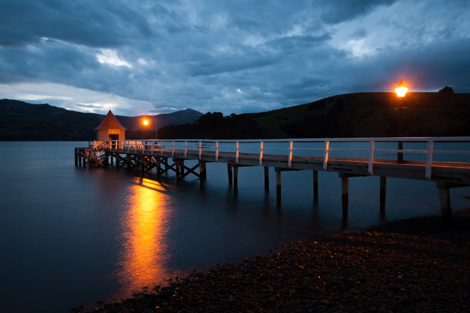 pier or jetty in Akaroa, canterbury, new zealand at night with reflection on water