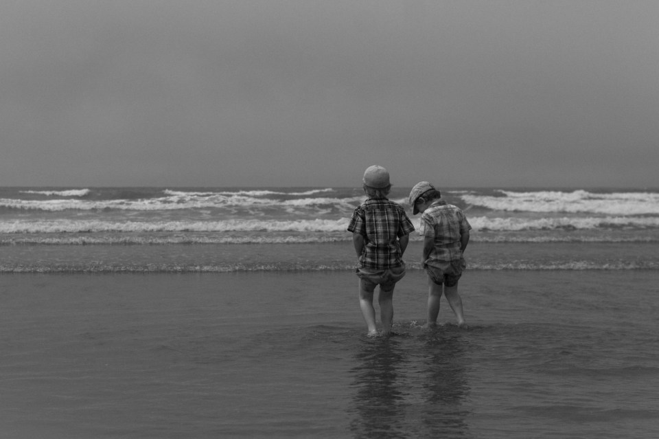 two boys playing in the water at the beach