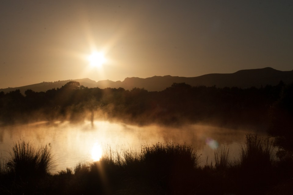 view at sunrise over a foggy lake in sepia