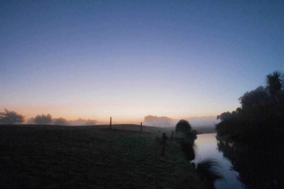 foggy morning before sunrise near river