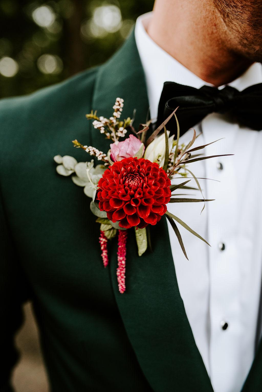 Donkergroen trouwpak met corsage