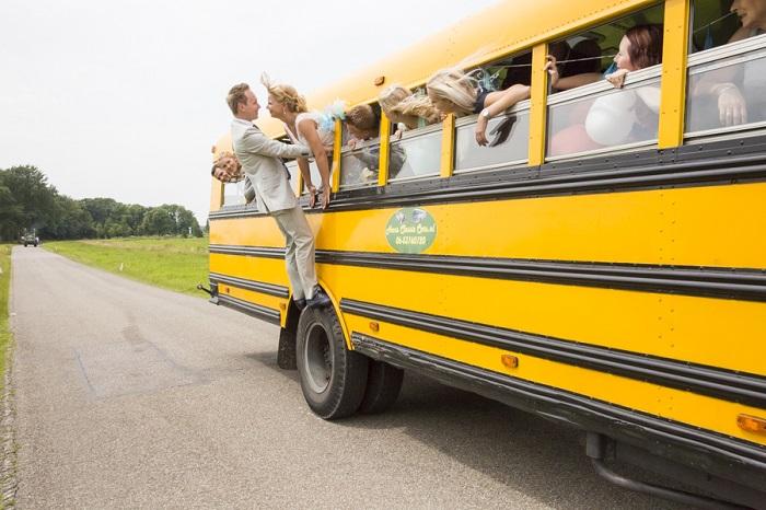 Bruidspaar en gasten in Amerikaanse schoolbus