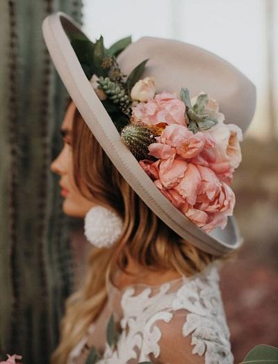Bruid met hoed vol bloemen
