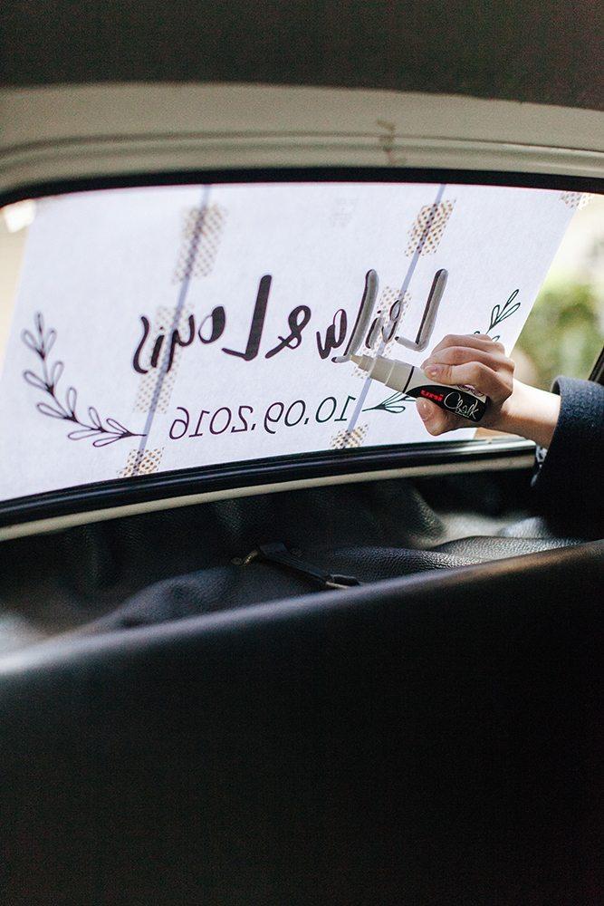 Raam van de trouwauto versieren met krijtstift