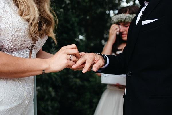Bruid schuift ring om vinger bruidegom