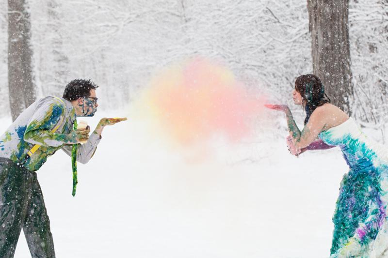 Bruidspaar in de sneeuw met gekleurd poeder