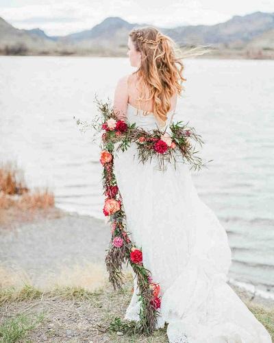 Bruid met rode bloemenslinger