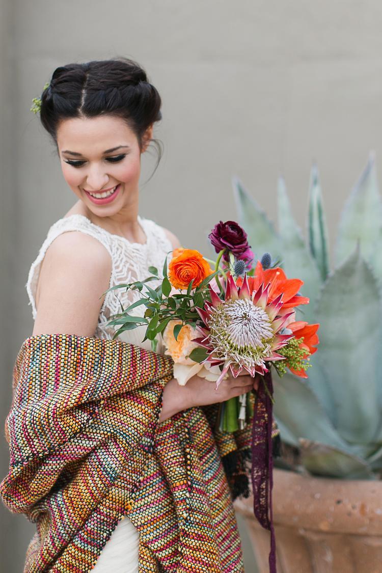 Bruid met gekleurde sjaal over haar trouwjurk
