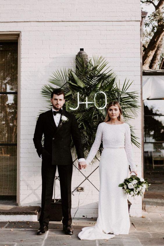 Bruidspaar onder witte neon letters