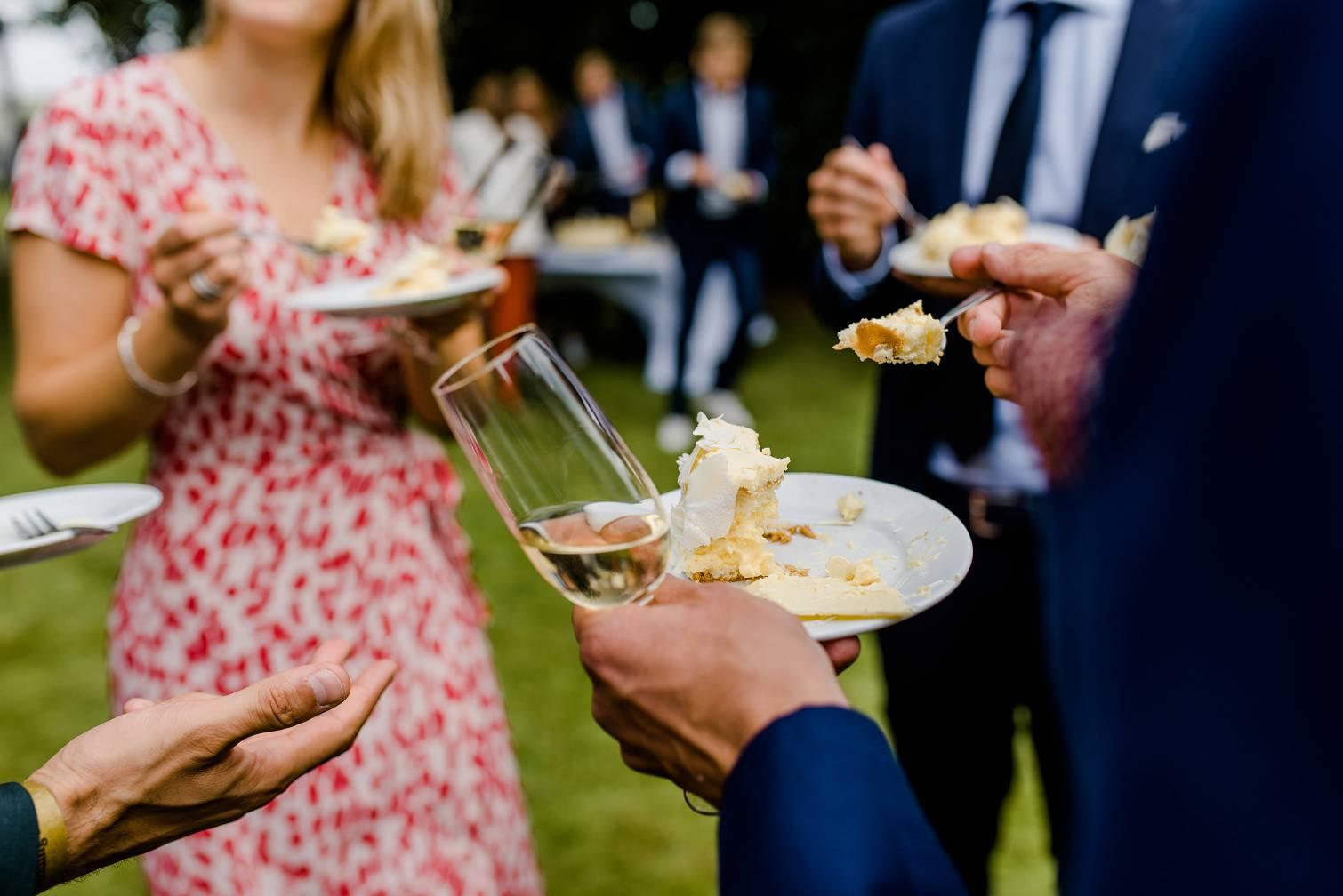 Gasten op de bruiloft receptie met taart in hun handen
