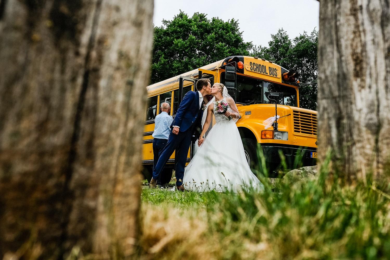 Kussend bruidspaar bij Amerikaanse schoolbus