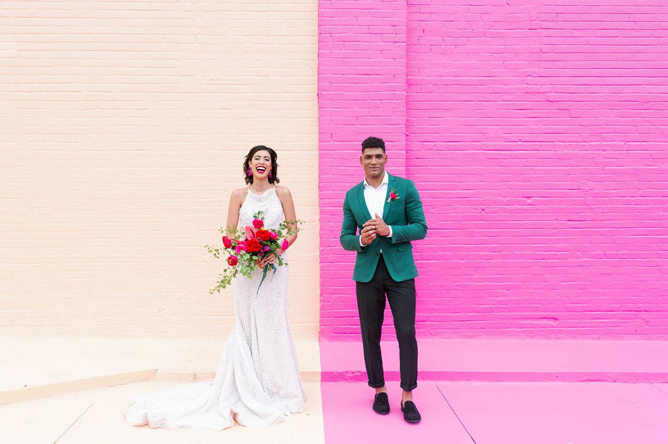 Bruidspaar voor een gekleurde muur