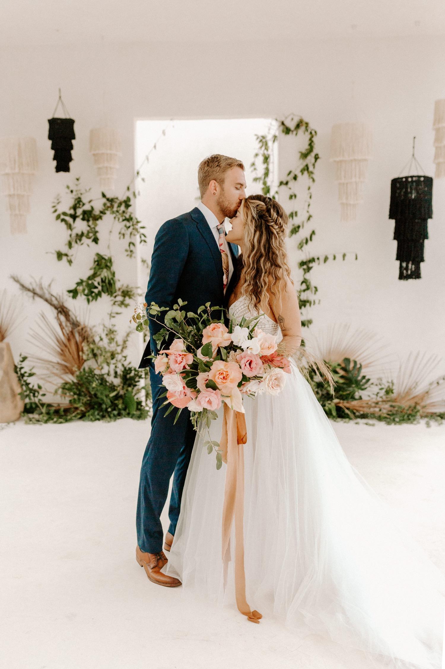 Bruidegom geeft bruid een kus op haar voorhoofd