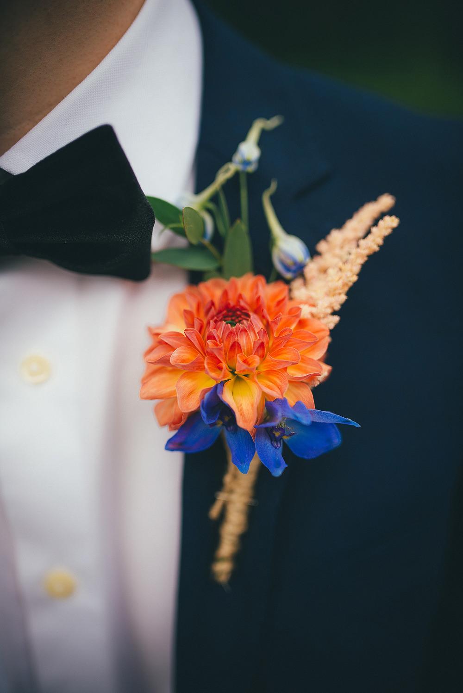 Oranje bruiloft corsage met grote bloem