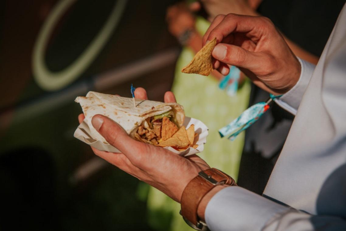 Bruiloft gast met foodtruck snack in zijn hand