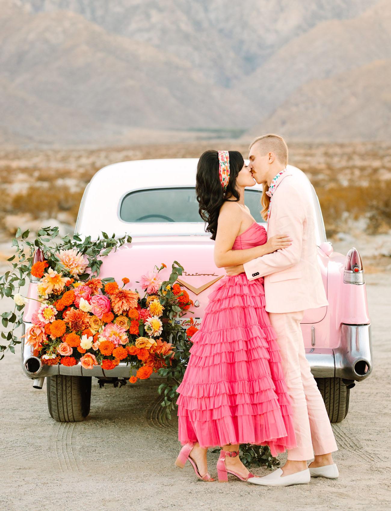 Bruidspaar bij roze Cadillac