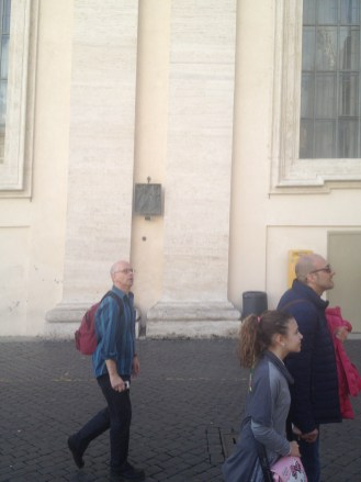 Catholics would recognize the square plaque behind the man with the red backpack. It's one of the stations of the cross. These plaques were located in St. Peter's Square.