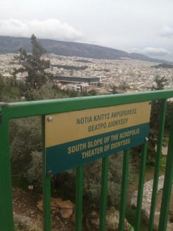 A sign indicating the Theater of Dionysus from atop a hill at the Acropolis.
