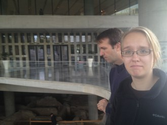 Standing outside the Acropolis Museum. Right outside there's a balcony that overlooks ruins that are below the museum.