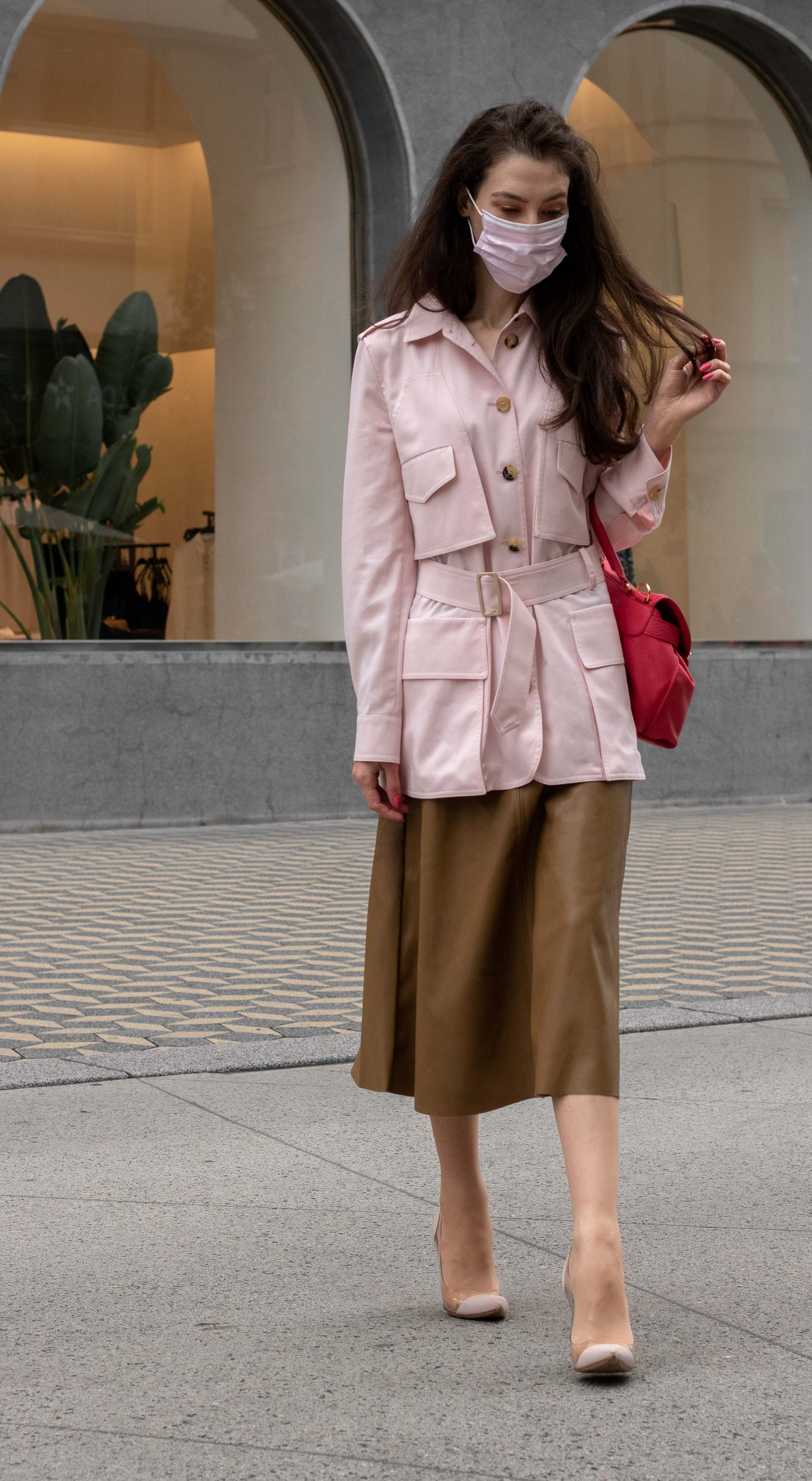 Fashion blogger Veronika Lipar of Brunette from Wall Street wearing Max Mara safari jacket H&M leather midi skirt Gianvito Rossi pumps face mask for work in fall