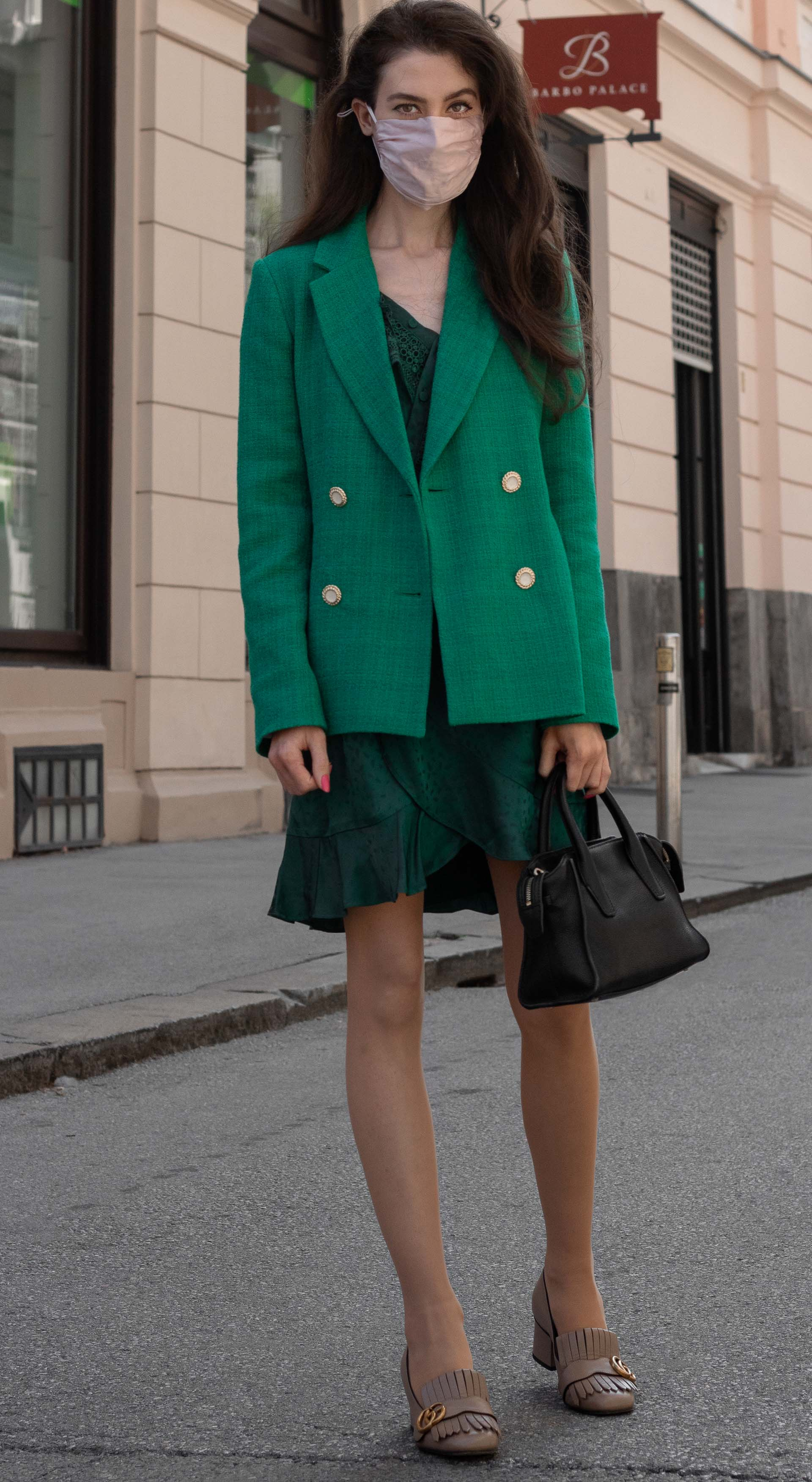 Fashion blogger Veronika Lipar of Brunette from Wall Street wearing Sandro Paris double breasted green blazer self-portrait wrap dress Gucci heeled loafers black bag face mask for office in fall