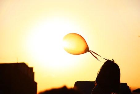 Una niña hace volar un globo sobre el ocaso del Sol